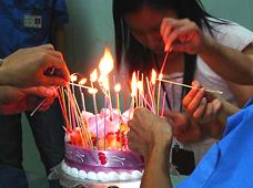 Chinese workers lighting a birthday cake for Michael Hammers